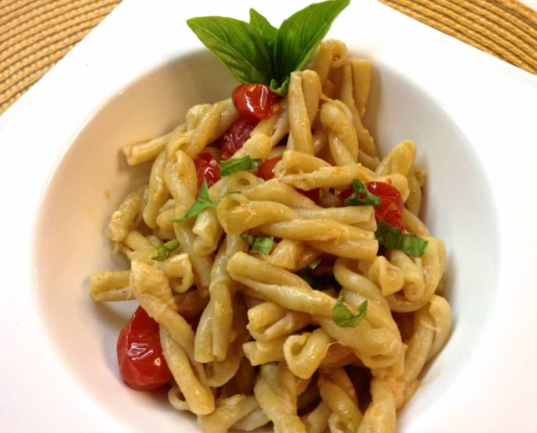 An overhead view of a square bowl of Gemelli Pasta with Tomatoes, Basil and Garlic