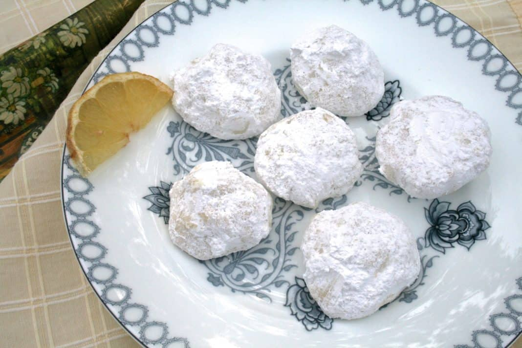 An overhead view of a plate of six Lemon Drop Cookies coated in powdered sugar and garnished with a lemon slice