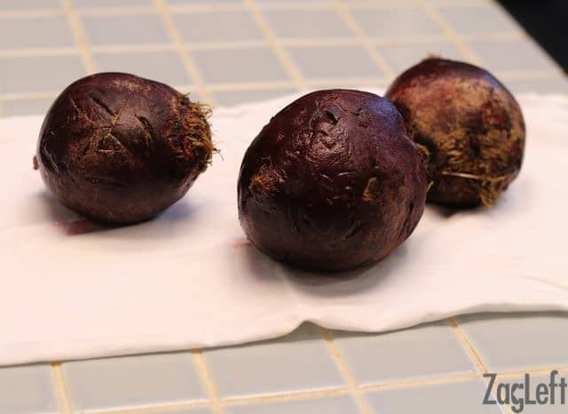 Three scrubbed beets on a cloth napkin