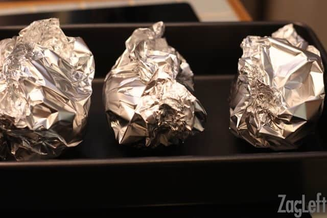 Three beets wrapped in aluminum foil on a baking tray